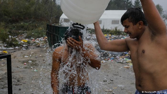 Man tipping water from canister over other man (Foto: Reuters/M. Djurica)