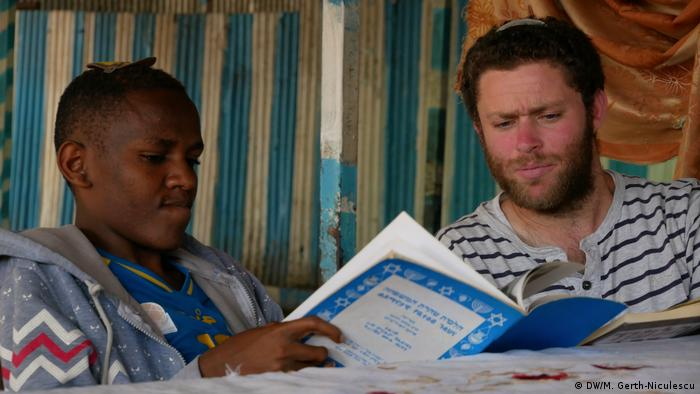Two Jewish men, an Ethiopian and an Israeli sit over a book