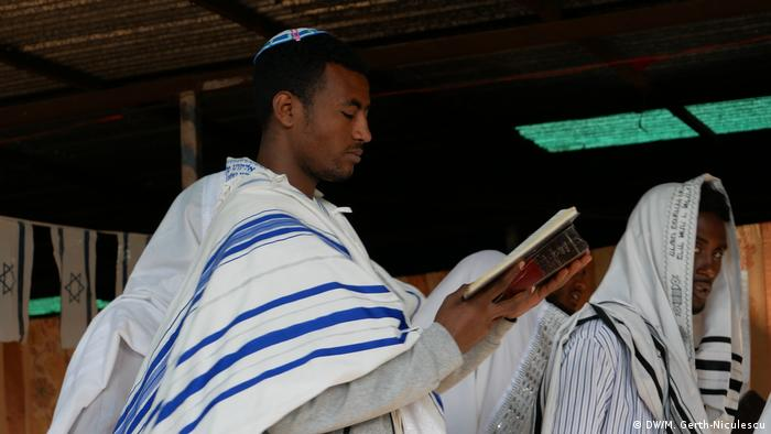 Man in keppi and white and blue shawl leading the Jewish prayer