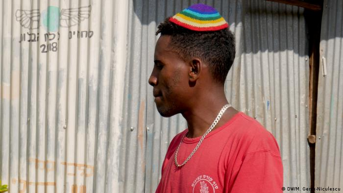 Man in a rainbow-volored kippa and red t-shirt