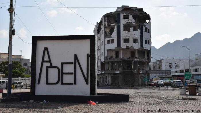 A sign for the city of Aden, with a bombed building behind it