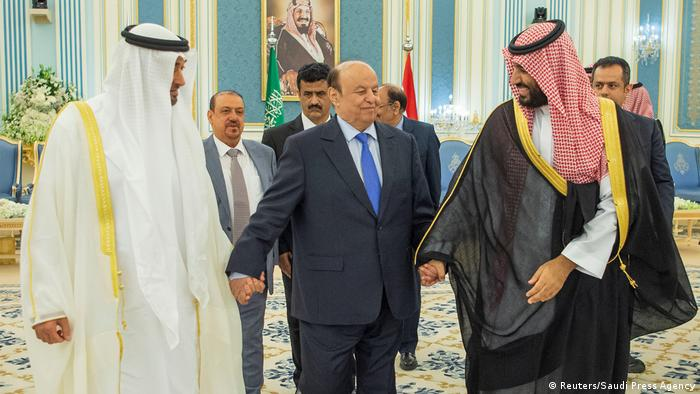 Abu Dhabi's Crown Prince Sheikh Mohammed bin Zayed al-Nahyan on the left, Saudi Crown Prince Mohammed bin Salman on the right and Yemen's President Abd-Rabbu Mansour Hadi stands in the center during a signing ceremony