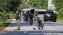 Members of a bomb squad inspect the site of an attack by suspected Muslim militants in Yala province on November 6, 2019. - At least fifteen people were killed and another four injured in attacks by suspected Muslim militants in Thailand's violence-wracked south, an army spokesman said on November 6, the largest death toll in years. (Photo by TUWAEDANIYA MERINGING / AFP)