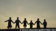 Sechs Kinder als Silhouette, spazieren über eine Wiese, halten die Hände