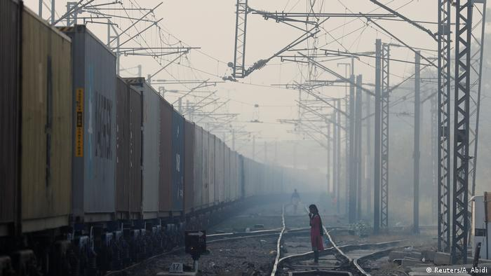 Child crosses train tracks in Indian smog