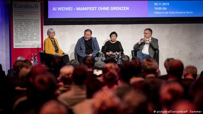 Ai Weiwei on stage in Berlin with a moderator, translator and German official