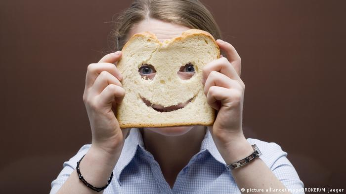 Person holding a piece of bread with a smiley face cut out of it in front of their face