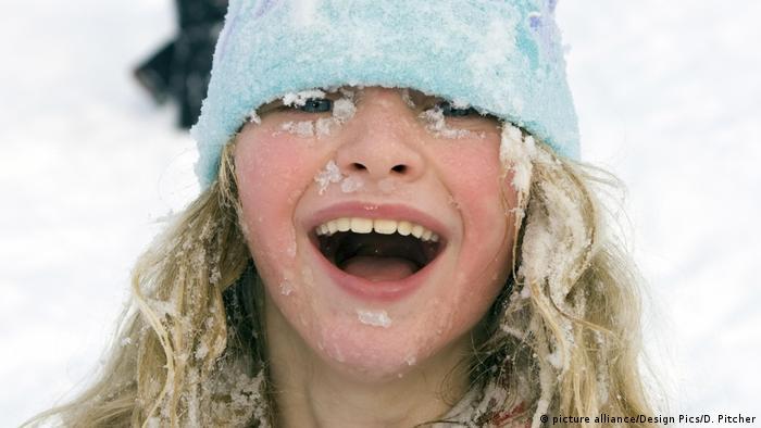 Gesicht eines lachenden Mädchens, das Gesicht, die Haare und die Mütze voll Schnee