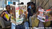 Men read the last edition of local newspapers in Addis Ababa on October 12, 2019, with the news of Ethiopian Prime Minister Abiy Ahmed's award of The Nobel Peace Prize the previous day. - Ethiopian Prime Minister Abiy Ahmed was urged to press on with reforms and efforts to heal bitter tensions with neighbour Eritrea after he won the Nobel Peace Prize on October 11, 2019. Abiy, hailed by the Nobel Committee for his efforts to achieve peace and international cooperation, sparked a historic rapprochement with longtime foe Eritrea soon after coming to power last year. (Photo by Michael TEWELDE / AFP) / The erroneous mention appearing in the metadata of this photo has been modified in AFP systems in the following manner: Byline should read [Michael TEWELDE] instead of [Tony KARUMBA]. Please immediately remove the erroneous mention[s] from all your online services and delete it (them) from your servers. If you have been authorized by AFP to distribute it (them) to third parties, please ensure that the same actions are carried out by them. Failure to promptly comply with these instructions will entail liability on your part for any continued or post notification usage. Therefore we thank you very much for all your attention and prompt action. We are sorry for the inconvenience this notification may cause and remain at your disposal for any further information you may require. (Photo by MICHAEL TEWELDE/AFP via Getty Images)