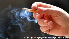 qualmende Zigarette in einer Hand