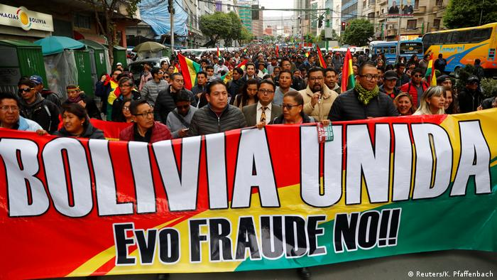 An oppposition banner during a protest reads united Boliva, Evo no fraud