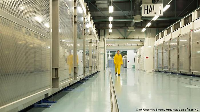 A man in a yellow suit walks down a metal-lined corridor in Fordow nuclear plant