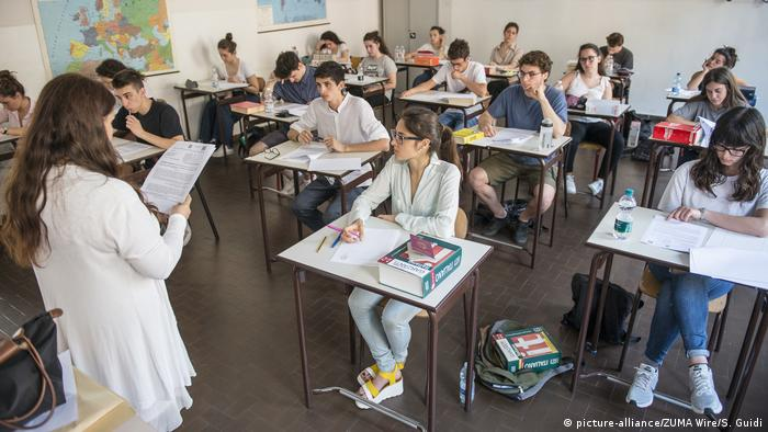 Pupils sit at desks in a small classroom in Italy
