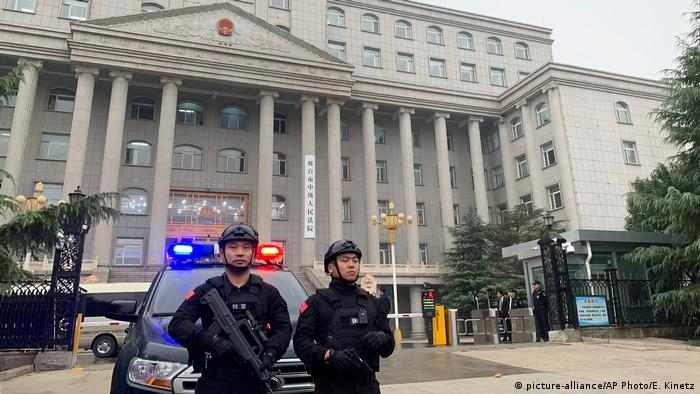 Two police officers in front of a court house in China