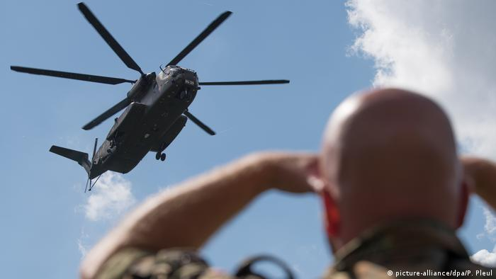 A Bundeswehr helicopter flies over a German soldier