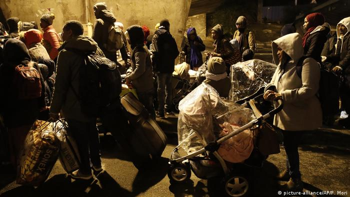 Migrants leave the site of makeshift camps as police officers clear the area in Paris, France