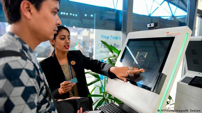 An airport staff member shows a passenger how to register his personal details at a facial recognition counter at the Rajiv Gandhi International Airport in Hyderabad