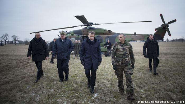 French President Emmanuel Macron walks after a flight aboard a NH90 helicopter