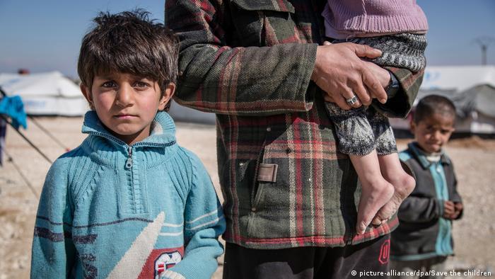 Siedmioletni Ibrahim obok ojca i siostryw obozie dla uchodźców