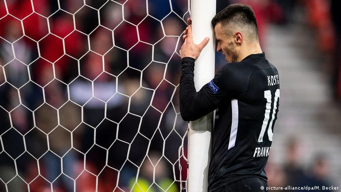 Frankfurt's Filip Kostic bangs his head against the goal post in frustration after his late miss against Standard Liege. (picture-alliance/dpa/M. Becker)