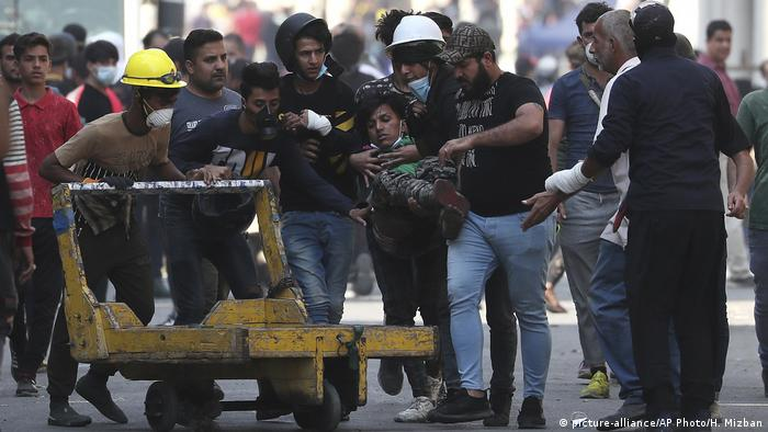 Anti-government protesters in Iraq carry a wounded man