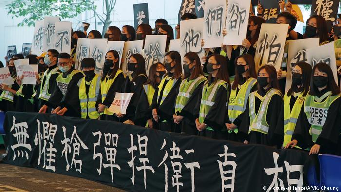 Maskierte Hongkonger Studenten singen bei ihrem Abschluss