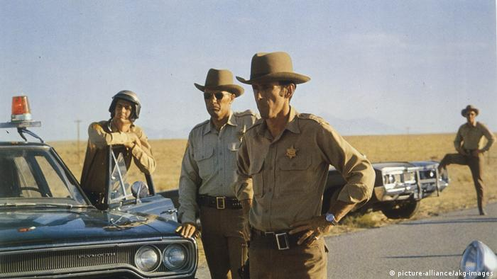 Filmstill Vanishing Point, 4 sheriffs standing on a road (picture-alliance/akg-images)