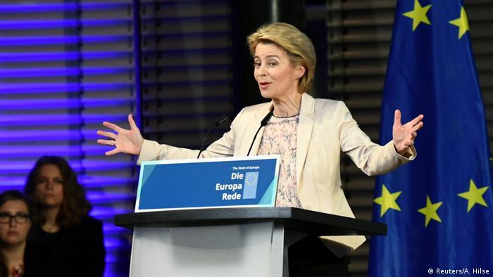 Урсула фон дер Ляйен перед микрофоном и флаг ЕС
