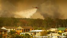 An Air-crane water bombing helicopter drops water on a bushfire in Harrington, Australia, November 8, 2019. AAP Image/Shane Chalker/via REUTERS ATTENTION EDITORS - THIS IMAGE WAS PROVIDED BY A THIRD PARTY. NO RESALES. NO ARCHIVE. AUSTRALIA OUT. NEW ZEALAND OUT.
