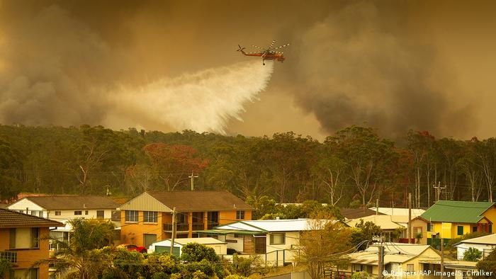 Plane distributing water about the bushfire in Harrington, Australia (Reuters/AAP Image/S. Chalker)