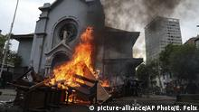 Items removed from a church by anti-government protesters go up in flames in a barricade built by the protesters, in Santiago, Chile, Friday, Nov. 8, 2019. Hooded protesters removed furniture and religious items from the church and set them on fire near the main gathering site of massive demonstrations in the capital over inequality. (AP Photo/Esteban Felix) |