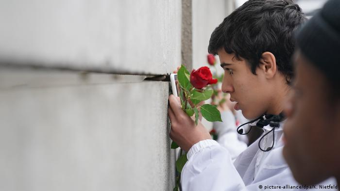 A Norwegian youth looks through a gap in a surviving section of the Berlin Wall (picture-alliance/dpa/K. Nietfeld)