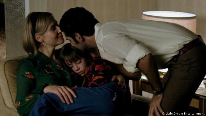 Film still Tomorrow we are free , a man bends to kiss a child asleep on a woman's lap (Little Dream Entertainment)