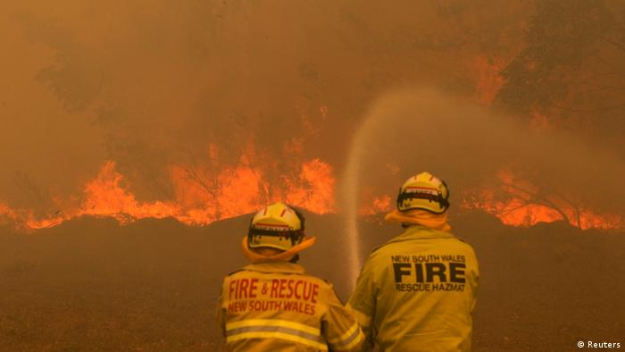 Two firemen fighting a wildfire