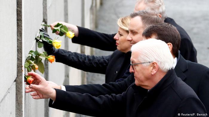 Пять президентов вставляют розы в щели Берлинской стены