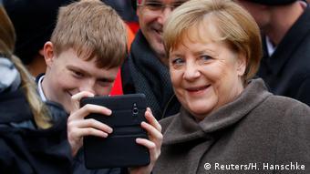 Меркель позирует для селфи с юношей
