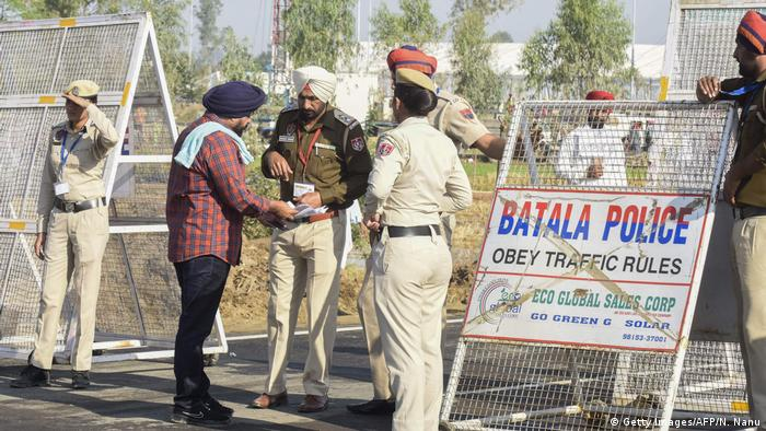 A pilgrim shows his documents to police at Kartarpur
