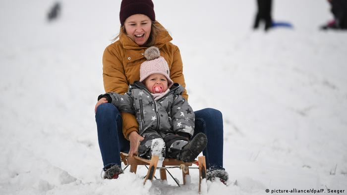 A woman and her child ride a sled on the Feldberg (picture-alliance/dpa/P. Seeger)