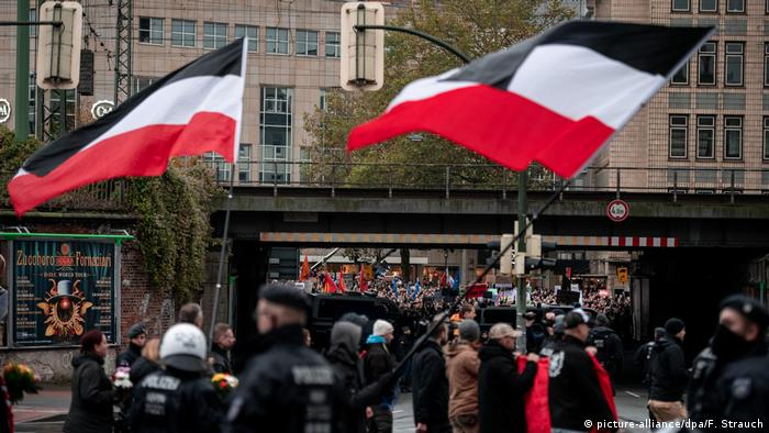 Neo-Nazi protesters take part in a march in Bielefeld while thousands of counterprotesters line the streets