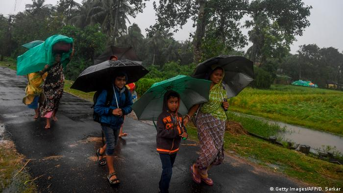 Villagers holding umbrellas carry their belongings on their way to enter a relief center as Cyclone Bulbul approaches in West Bengal, India