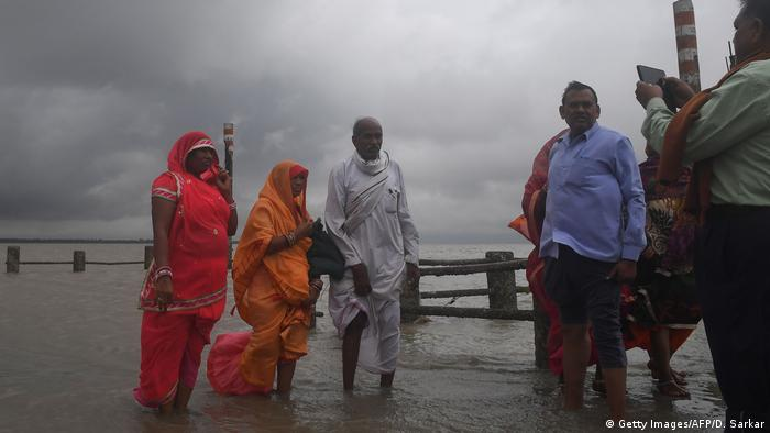 People wade through the water in West Bengal state as Cyclone Bulbul approaches