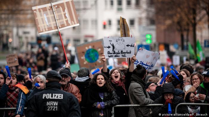 Manifestantes gritam diante de barricada defendida por policial alemão