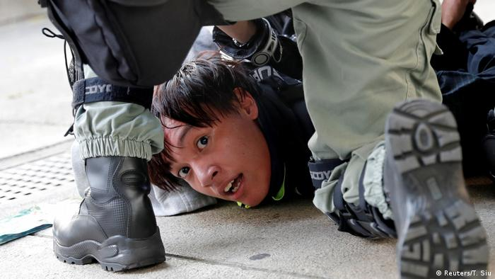 Protester on the ground with police holding him down (Reuters/T. Siu)