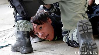 Αστυνομικοί ακινητοποιούν διαδηλωτή στον δρόμο