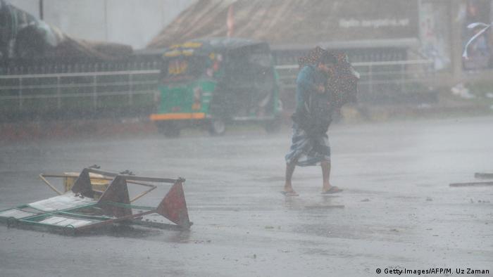 Pedestrian attempts to walk amid heavy wind and rain