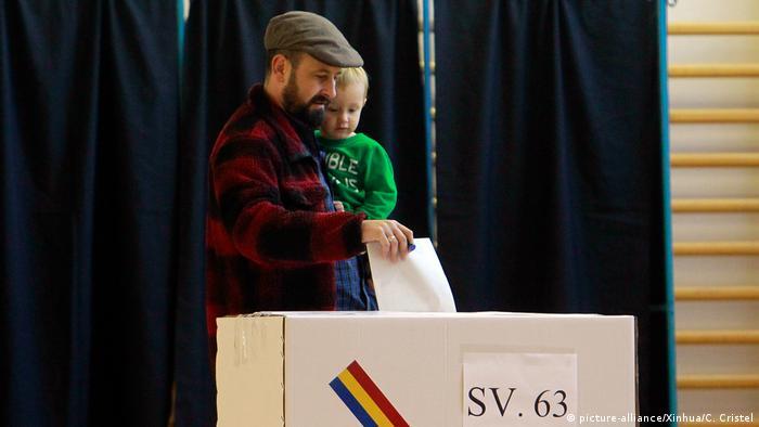 Un barbat cu un copil in brate la vot in 2019