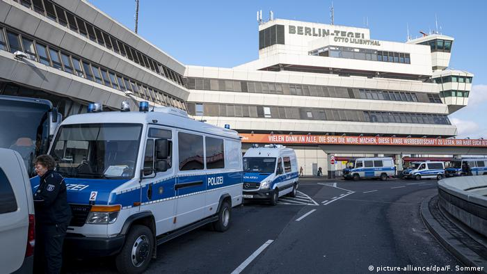 Police vehicles park outside of Berlin's Tegel Airport after climate protesters staged a sit-in at one of the terminals