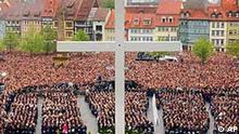 A cross stands in front of thousands of people during a funeral service and a mass on the steps of the Cathedral in Erfurt, eastern Germany, on Friday, May 3, 2002, seven days after a 19-year-old former student shot 16 people before killing himself in a rampage shooting at the city's Gutenberg high school, Friday April 26. (AP Photo/Jens Meyer, Pool)