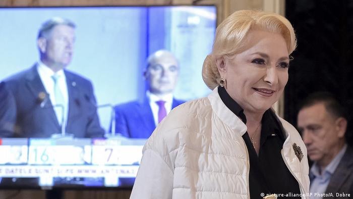 În prim plan, contracandidata lui Iohannis, şefa PSD, V.V. Dăncilă. Pe fundal,preşedintele şi favoritul celui de-al doilea tur al scrutinului, alături de politicianul PNL, Rareş Bogdan.