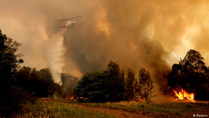 A fire bombing helicopter works to contain a bushfire